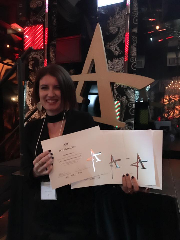 Madalina Iordache-Levay holds up BrightPink Studio Silver ADDY Awards for web design and responsive design